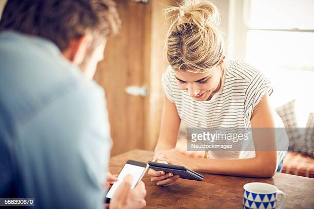 Woman using digital tablet with man in foreground in kitchen