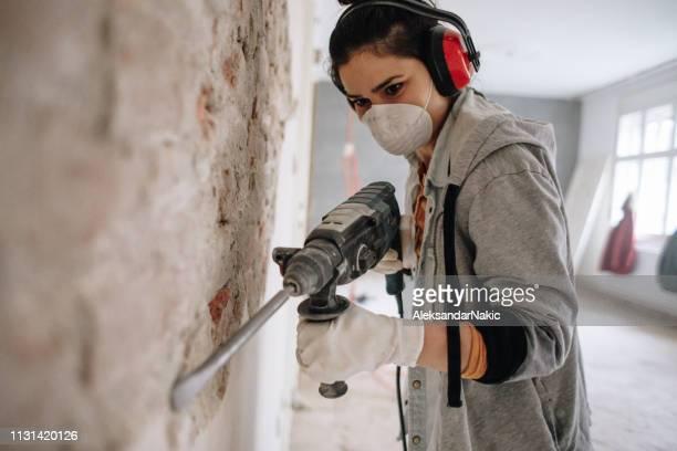 vrouw met behulp van boormachine tijdens de wederopbouw van haar appartement - doe het zelven stockfoto's en -beelden