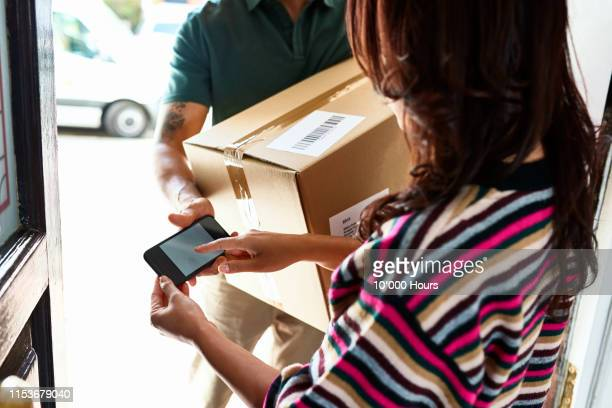 woman using electronic device to sign for parcel - day stock pictures, royalty-free photos & images