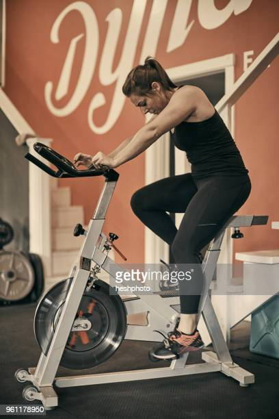 woman using exercise bike in gym - heshphoto stock pictures, royalty-free photos & images
