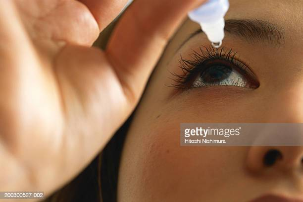 Woman using eye drops, close-up