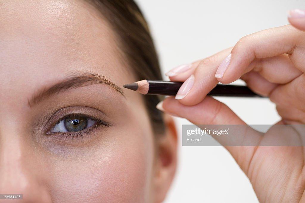Woman using eyebrow pencil : Stock Photo