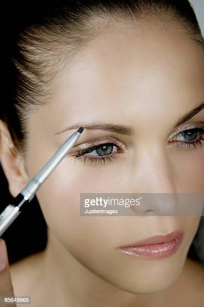 Woman using eyebrow pencil