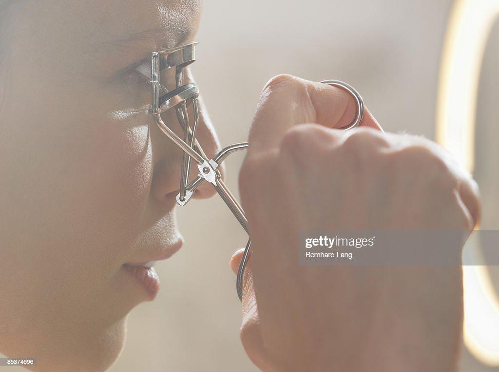 Woman (36y) using eyelash curler : Stock Photo