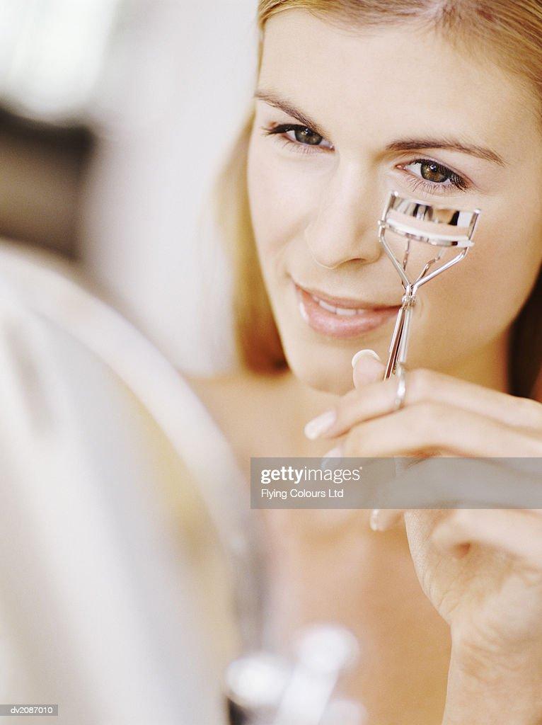 Woman Using Eyelash Curlers : Stock Photo