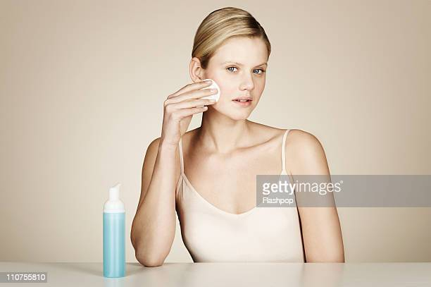 Woman using face cleanser