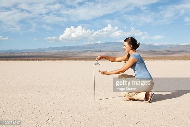 Frau mit Wasserhahn in Wüstenlandschaft