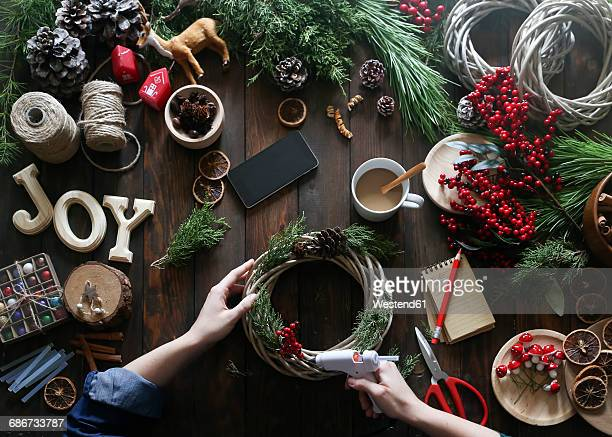Woman using glue gun for decorating Advent wreath, partial view