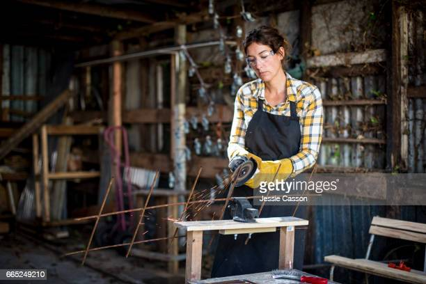 woman using grinder in workshop - molen stockfoto's en -beelden