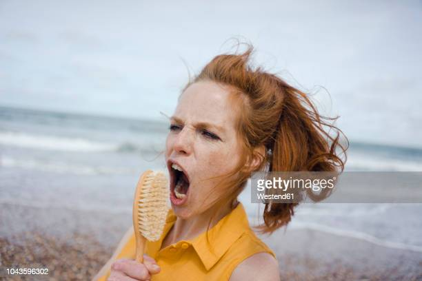 woman using hair brush at the sea as a microphone - singing stock pictures, royalty-free photos & images