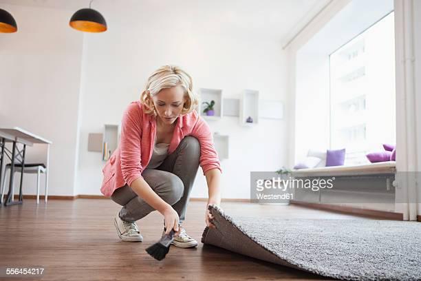 Woman using hand brush at living room