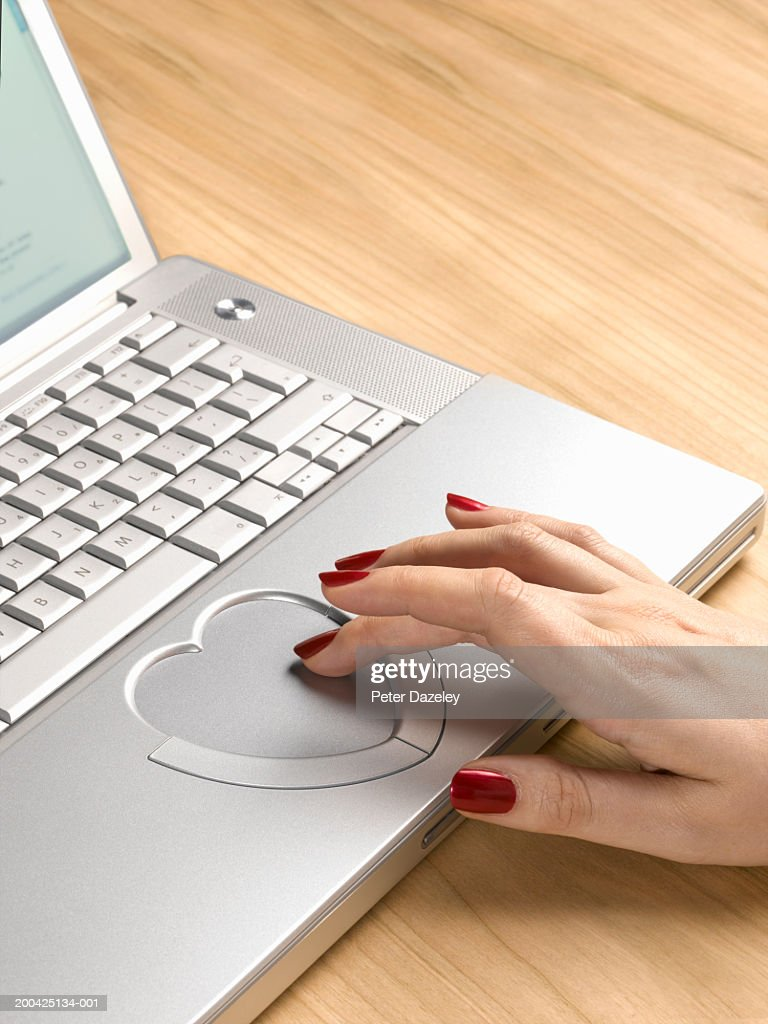 Woman using heart shaped  touch pad on laptop computer, close-up : Foto de stock