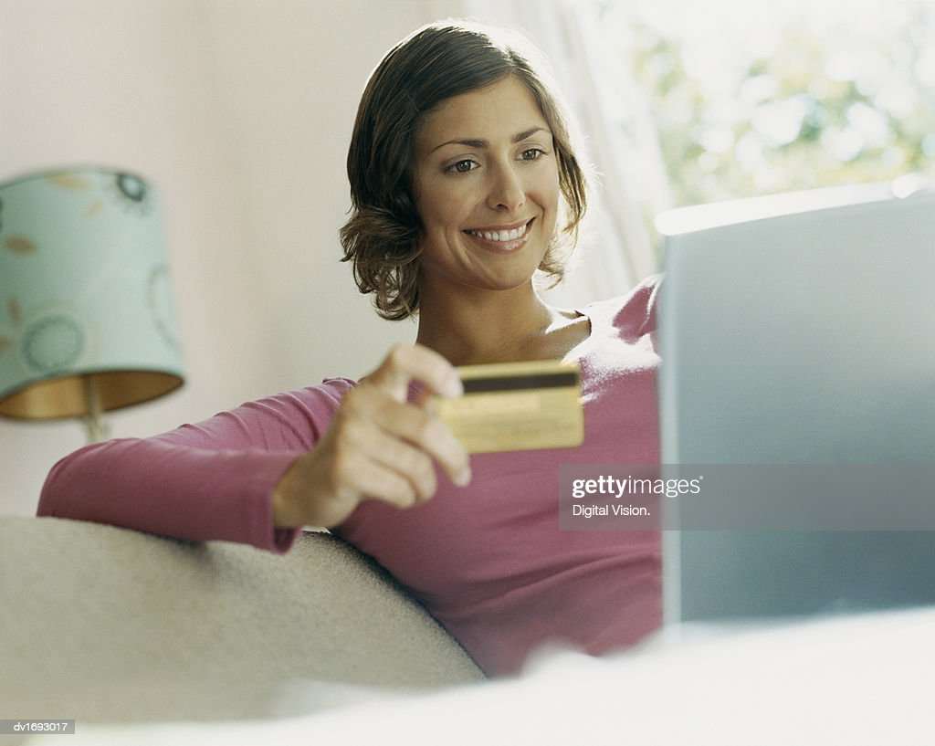 Woman Using Her Bank Card Online With a Laptop : Stock Photo