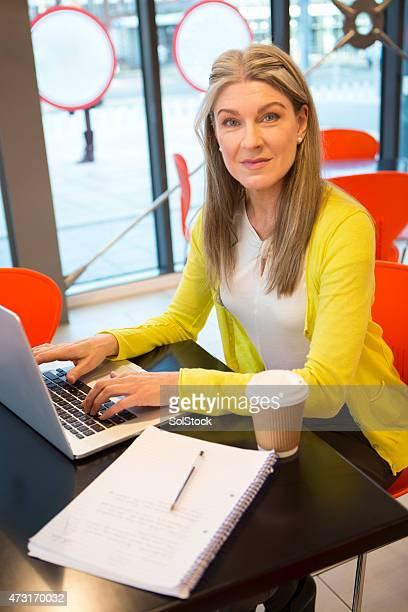 女性は彼女のラップトップを使用して、カフェ