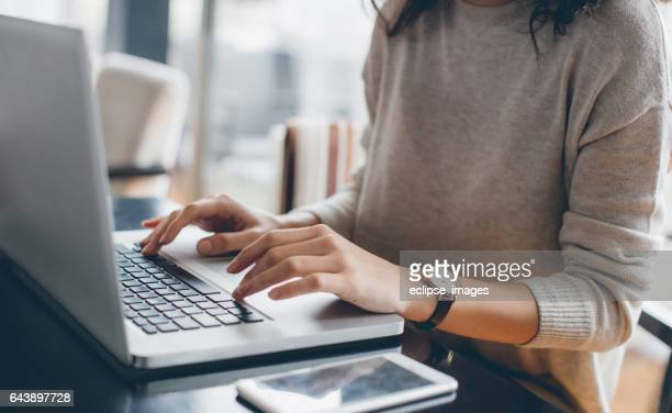 woman using her laptop - person on laptop stock pictures, royalty-free photos & images