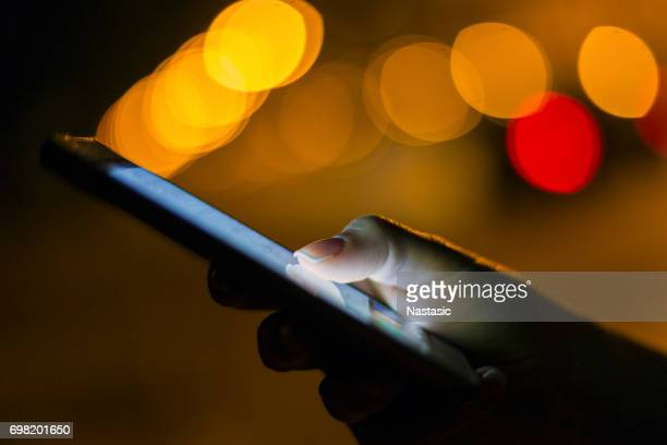 Woman using her mobile phone at night