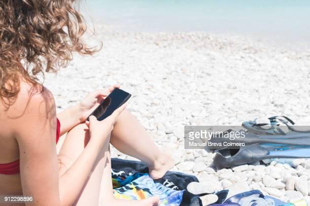 woman using her mobile phone in the beach - werkloosheid stockfoto's en -beelden