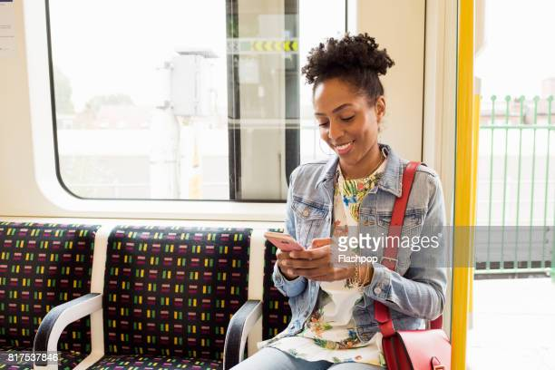 woman using her phone on a train - black purse stock pictures, royalty-free photos & images