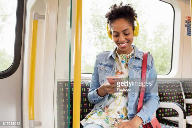woman using her phone on a train - rush hour stock pictures, royalty-free photos & images