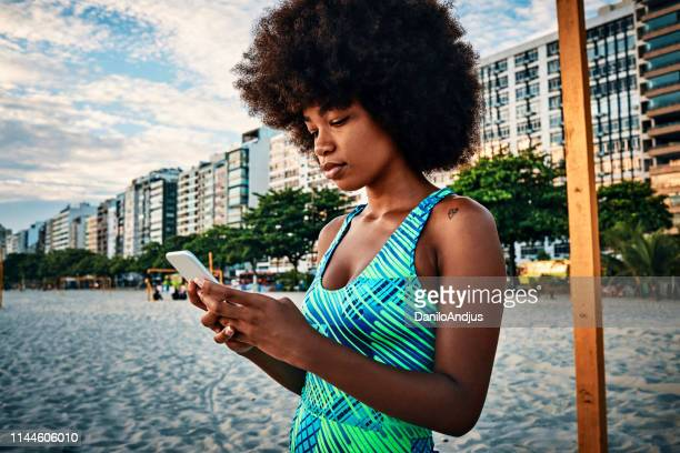 woman using her smartphone and enjoying the music after training - social media marketing stock pictures, royalty-free photos & images