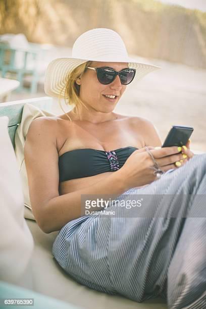 Femme à l'aide de son smartphone à la plage