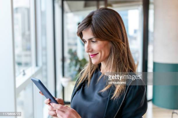 woman using her smartphone - pbs stock pictures, royalty-free photos & images