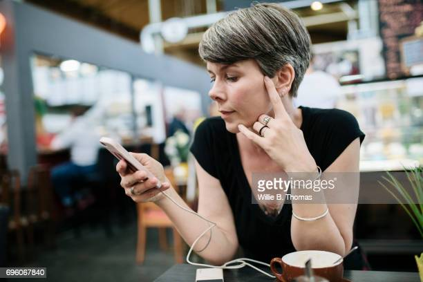 A Woman Using Her Smartphone While Sitting Down For Coffee