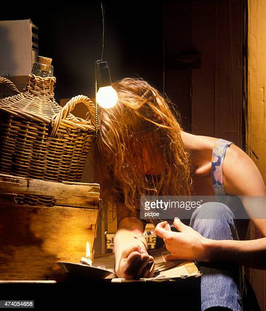 woman using heroin in grungy room - heroin addict arm stock photos and pictures