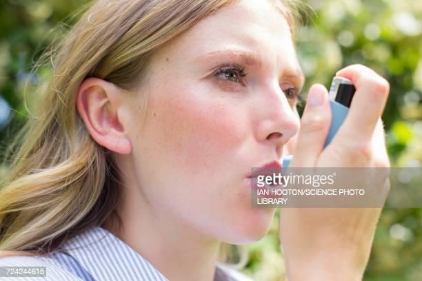 woman using inhaler - apparato respiratorio foto e immagini stock