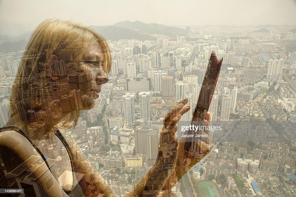 woman using ipad and cityscape : Stock Photo