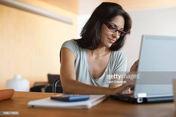 woman using laptop and cell phone - sending stock pictures, royalty-free photos & images