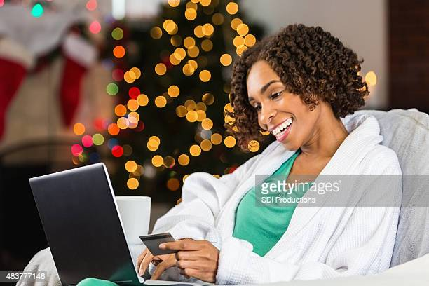 Woman using laptop and credit card to buy Christmas gifts