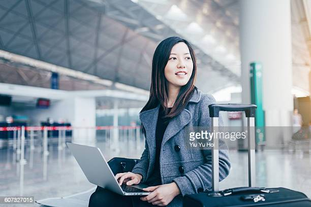 Woman using laptop and looking away at airport