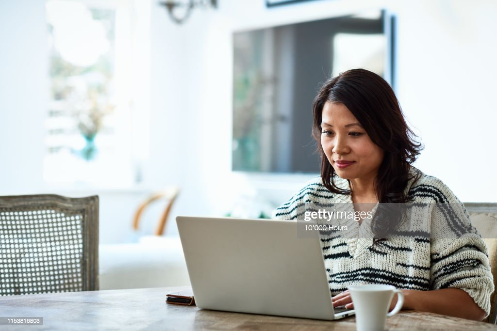 Woman using laptop and working from home : Photo