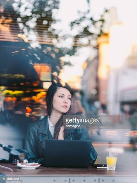 Woman using laptop at cafe