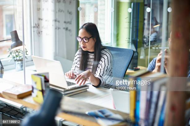 Woman using laptop at desk.