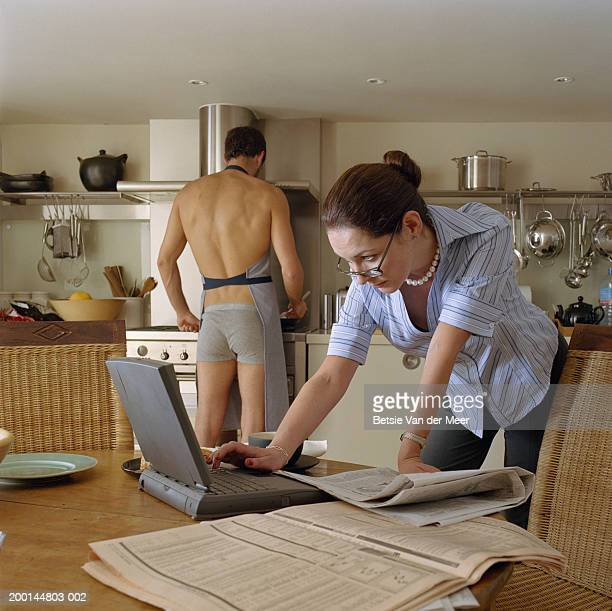 woman using laptop at kitchen table, semi-dressed man in background - cougar woman fotografías e imágenes de stock
