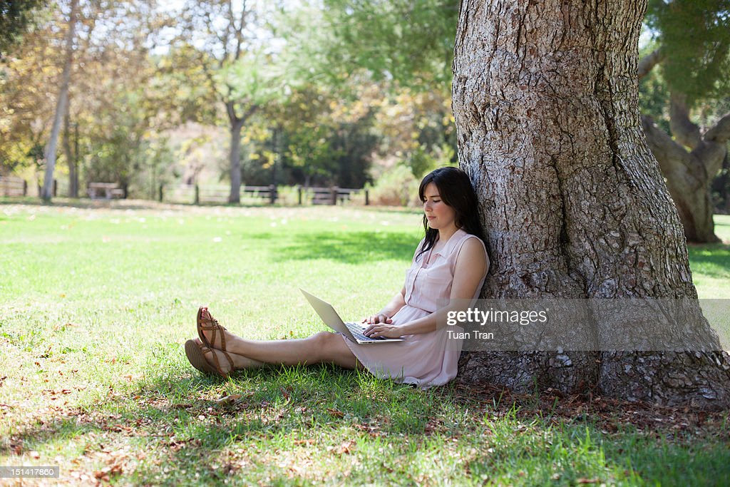 Woman using laptop at park : Foto de stock
