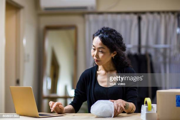 A woman using laptop at shop