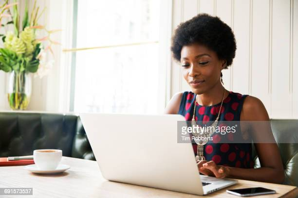 woman using laptop at table - using laptop stock pictures, royalty-free photos & images