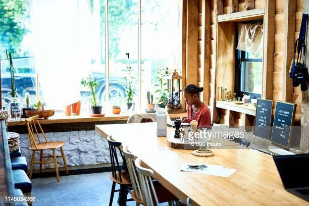 woman using laptop at wooden dining table - home office stock pictures, royalty-free photos & images
