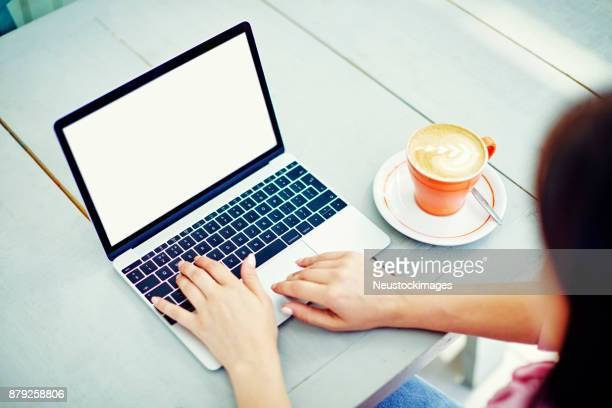 Woman using laptop by coffee cup on table at cafe
