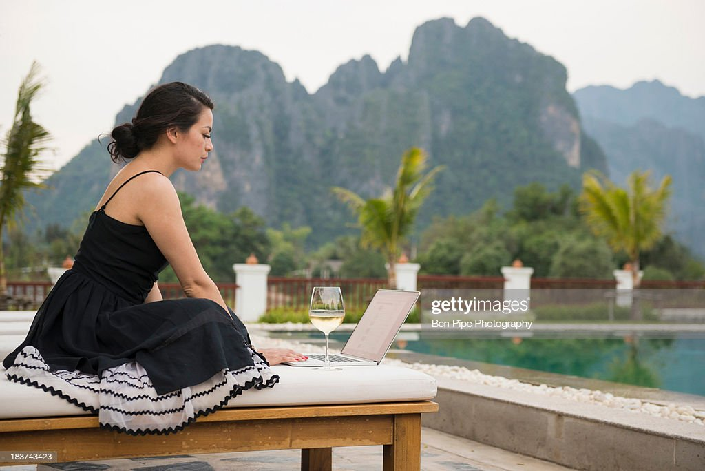 Woman using laptop by poolside, Vang Vieng, Laos : Stock Photo