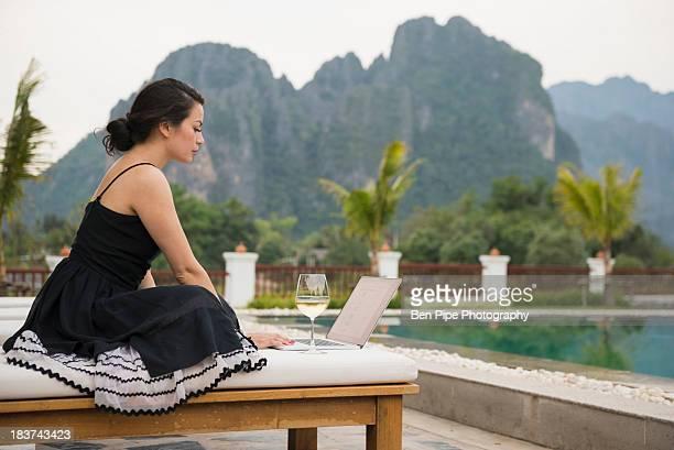 Woman using laptop by poolside, Vang Vieng, Laos