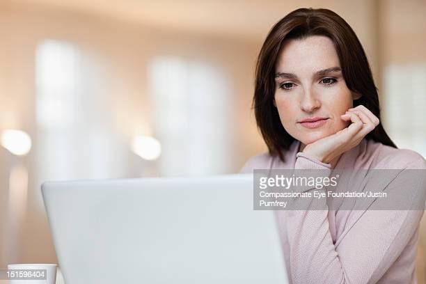 Woman using laptop, close up