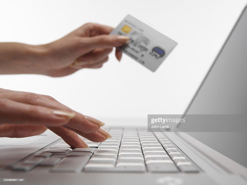 Woman using laptop computer, holding credit card, close-up : Stock Photo