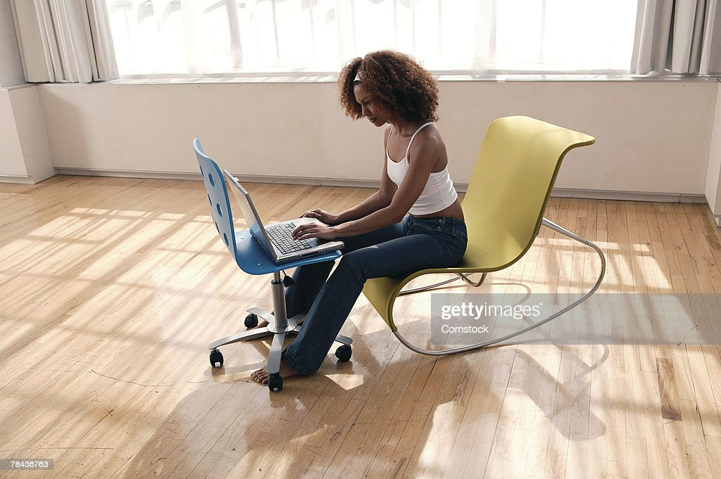 Woman using laptop computer in sunlit room : Stockfoto