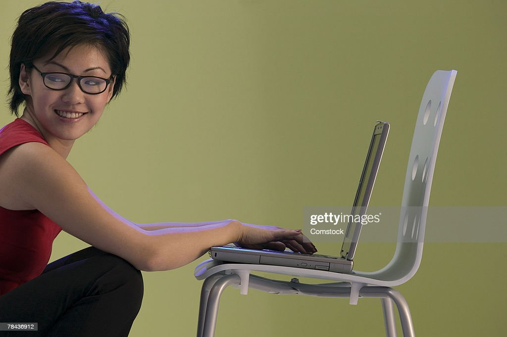 Woman using laptop computer on chairs : Stockfoto