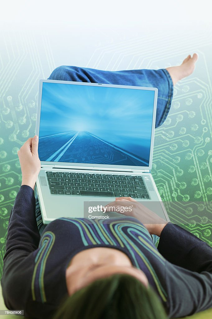 Woman using laptop computer with information superhighway : Stockfoto