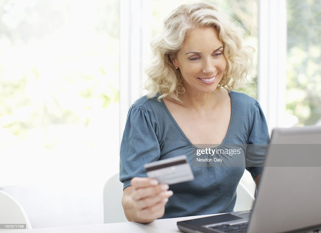 Woman using laptop, holding credit card, smiling : Foto de stock